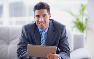 Businessman Sitting On Sofa Using His Tablet Smiling At Camera I